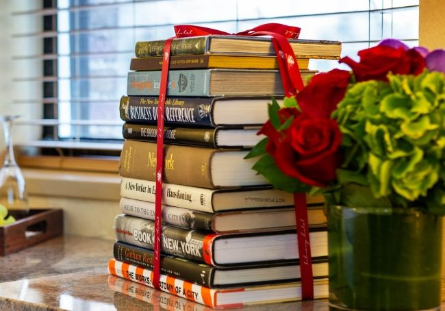 Stack of hand selected books and floral arrangement.