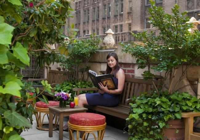 Woman reading on Library Hotel Rooftop Terrace