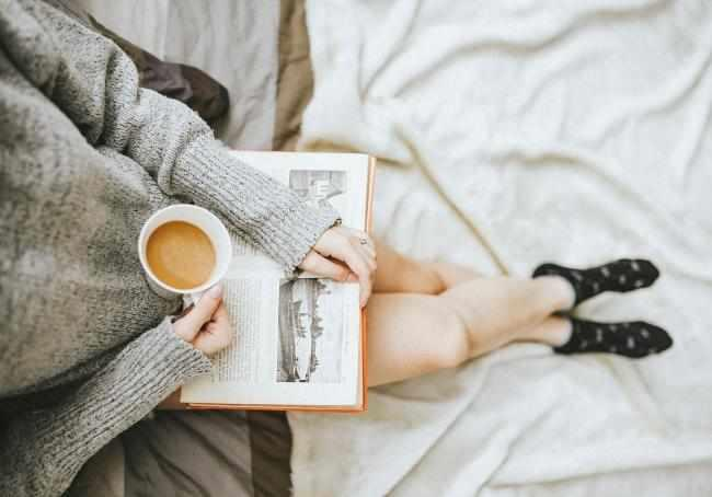 Woman cozy with a book and coffee