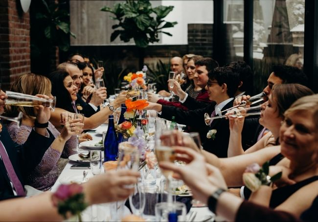 family toasting to bride and groom around the table