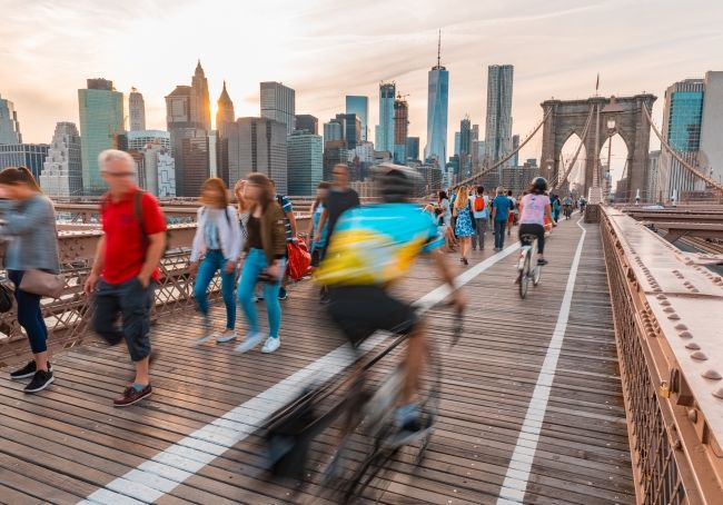 People walking and riding bikes on Brooklyn Bridge.