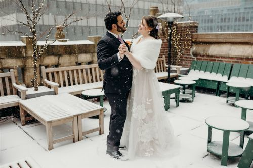 The New Mr. & Mrs. enjoying a picturesque snowfall as the perfect touch to our rooftop terrace photo spot. Photo by: Lauren Spinelli Photography