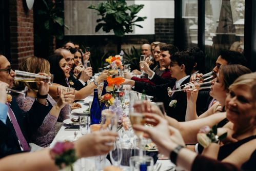Family and friends gathered around the table in the Writer's Den Enclosed terrace toasting to the Bride and Groom. Photo by: Lauren Spinelli Photography