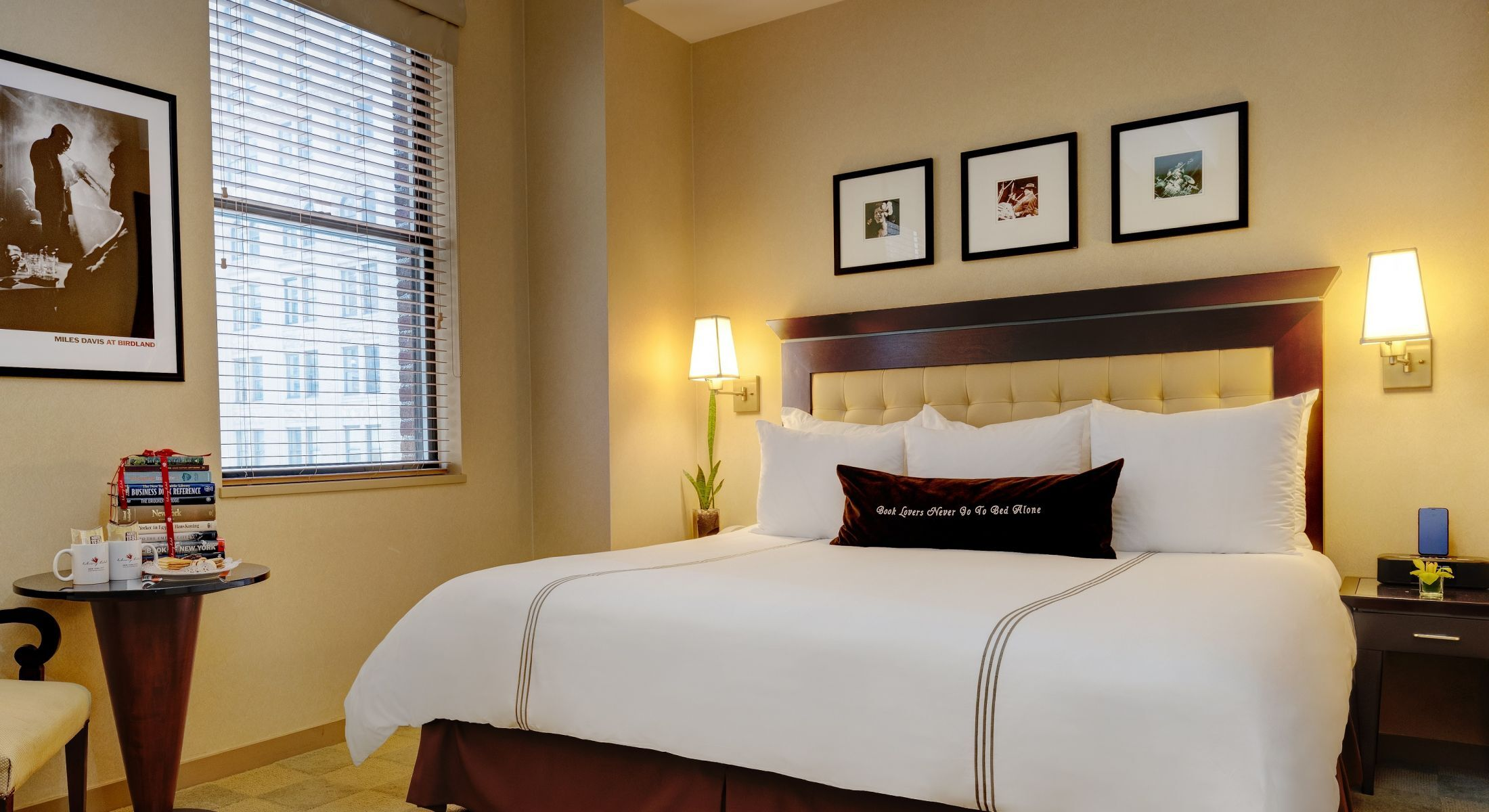 King bedded room with 2 nightstands and table with special added amenities